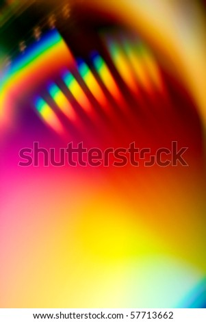A closeup view of the rainbow reflection of light from a compact disk or CD, suitable for a colorful background - stock photo
