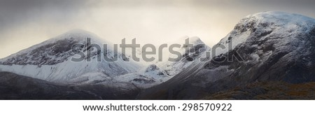 A cloud and snow capped summit of Beinn Eighe in the Scottish Highlands. - stock photo