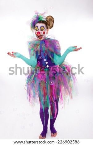A clown is happy about flying blow bubbles - stock photo