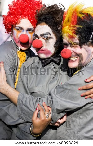 A Clown Stuck In The Middle With Clowns To The Left And Jokers To The Right - stock photo