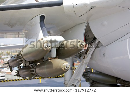 A cluster of bombs mounted under the wing of a modern fighter aircraft - stock photo