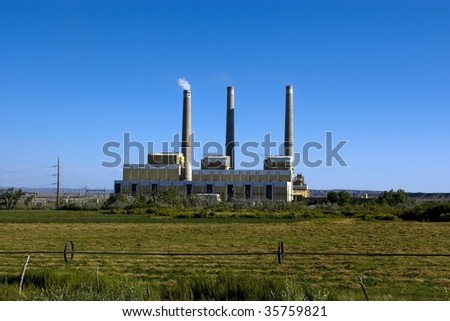 A coal fired power plant with a hay field in front.