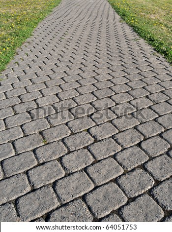 A cobblestone path with square bricks showing perspective. - stock photo