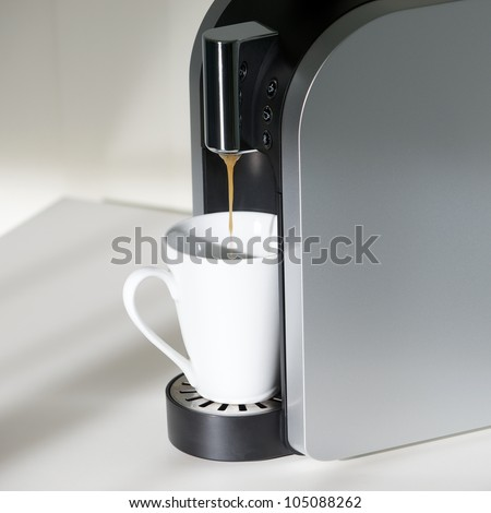 A coffe machine is brewing some coffee.