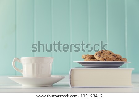 A coffee and some chocolate chip cookies over a book on a white wooden table with a robin egg blue background. Vintage style. - stock photo
