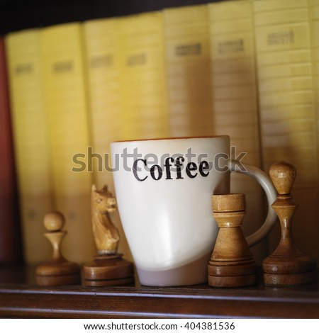 A coffee cup and chess pieces next to some books on a shelf, concept of intelligence. Indoor angled shot - stock photo
