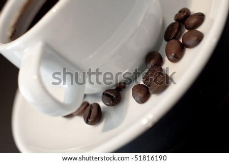 A coffee cup with coffee beans on the plate. - stock photo