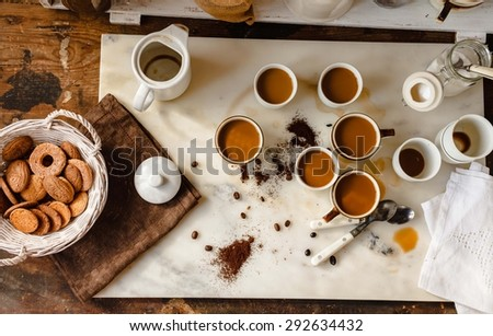 A coffee drink family breakfast concept. Concept include many cups with cappuccino and coffee drink situated over a marble rustic kitchen table with basket of biscuits from above. Rustic still life. - stock photo