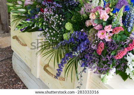 A coffin with a flower arrangement  - stock photo