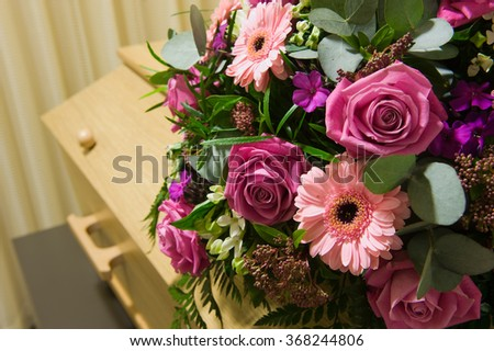 A coffin with a flower arrangement in a morgue - stock photo