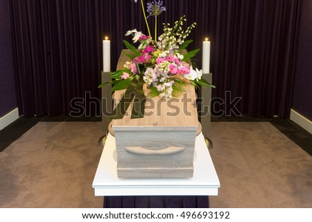 A coffin with flower arrangement in a morgue