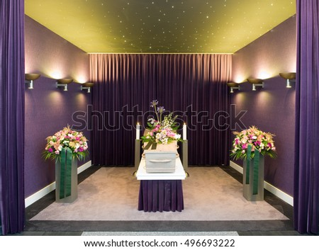 A coffin with flower arrangements in a morgue