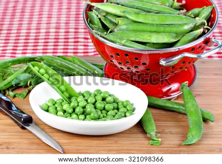 A colander full of fresh peas with peas being shelled on the side. - stock photo
