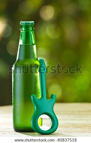 A cold bottle of beer with a guitar opener in the garden - stock photo