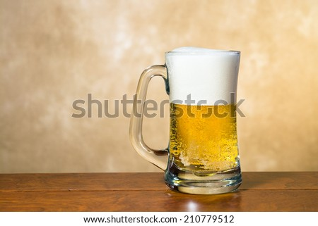 A cold, crisp mug of beer in a traditional pint glass with a foamy head - stock photo