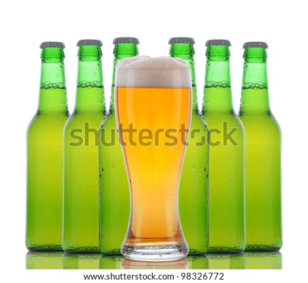 A cold frosty glass of beer in front of a group of green bottles on a white background. Horizontal with reflection.