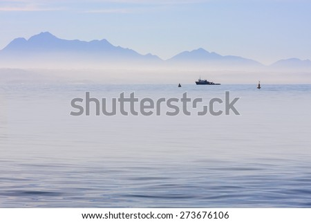 a cold misty ocean scene over tranquil calm water looking at a blue mountain skyline horizon with a working vessel moored in the distance - stock photo