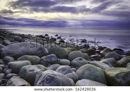 A cold sunset over the stony beach at Seaside, Oregon, USA. - stock photo