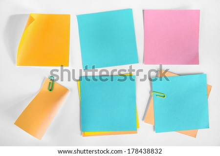 A collection of blank notes of different colors and shapes on white background.