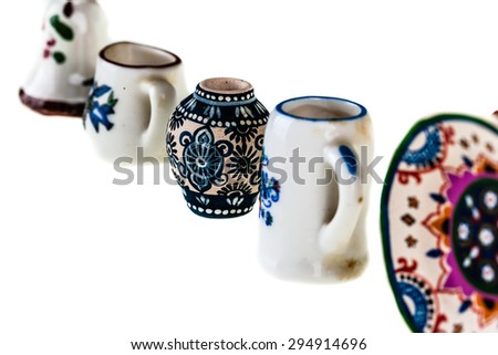 a collection of colorful bulgarian miniature tableware isolated over a white background - stock photo