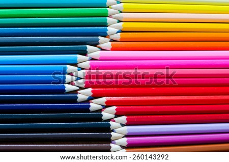 A collection of colourful pencil crayons lined up together in rows meeting at the tips. Whole image is top view horizontal. - stock photo
