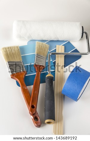 A collection of house painting supplies that includes a roller, paint brushes, paint samples, paint stir stick and painters tape. Copy space was provided and selective focus was used on this image. - stock photo