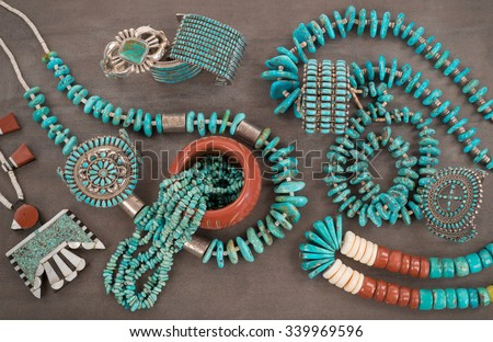 """A collection of Native American Jewelry.A Santo Domingo Depression Era Necklace, and Turquoise """"Nugget"""" with silver beads, and Zuni and Navajo """"Cuff"""" Bracelets, on a Grey Slate Background. - stock photo"""