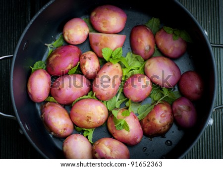 A collection of peeled new potatoes sprinkled with mint in a large black pot. - stock photo