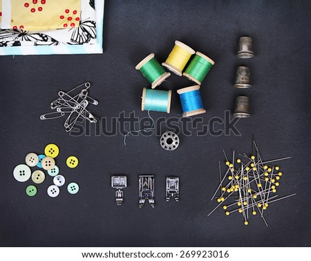A collection of sewing items including: thread, thimbles, pins, buttons, bobbin, sewing machine feet and material on a chalkboard background - stock photo