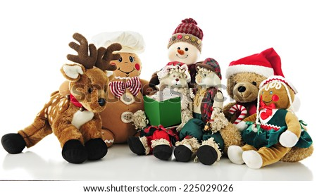 A collection of stuffed Christmas critters surrounding Ma Bunny who holds a Christmas carol book (or storybook) for the others to enjoy.  On a white background. - stock photo