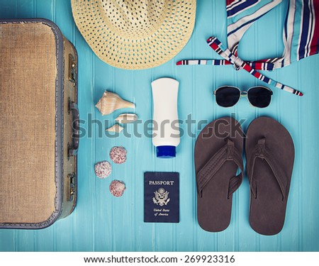 A collection of travel items including suitcase, passport, sandals, sunglasses, swim suit, sunscreen and straw hat on turquoise background - stock photo