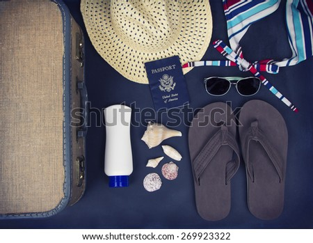 A collection of travel items including suitcase, passport, sandals, sunglasses, swim suit, sunscreen and straw hat on chalkboard background - stock photo