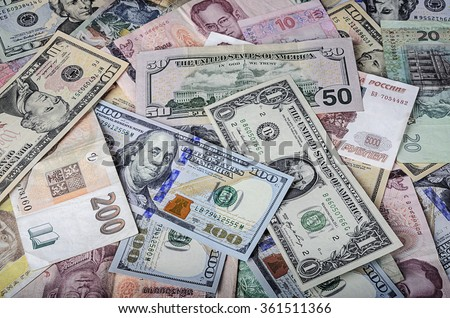 A collection of various foreign currencies from countries spanning the globe. Many different currencies as colorful background concept global money. Soft selective focus and shallow depth of field - stock photo