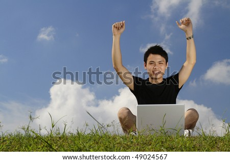 A college student and a laptop with his arms raised in triumph - stock photo