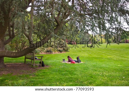 A college student on her laptop under a tree on a grassy field