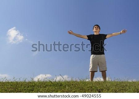 A college student with his arms raised while standing outdoors - stock photo