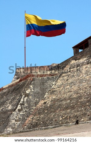 A Colombian flag is streaming in the wind over the weathered walls of the fortress of Castillo San Felipe de Barajas in Cartagena de Indias, Colombia. - stock photo