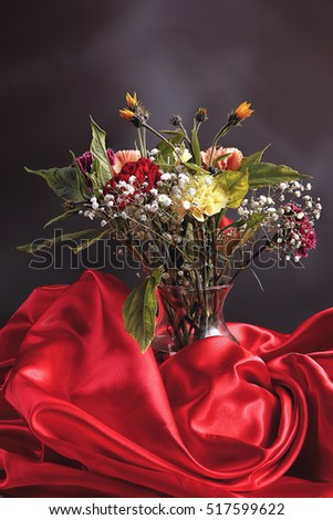 A color bouquet of carnations in a glass vase surrounded by a red cloth.
