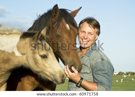 A color portrait photo of a handsome smiling man petting his beautiful horses.