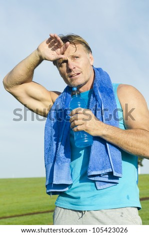 A color portrait photo of a handsome sportsman in his forties sweating after having a run in the park. He has a blue towel around his neck and is holding a blue water bottle in his hand. - stock photo