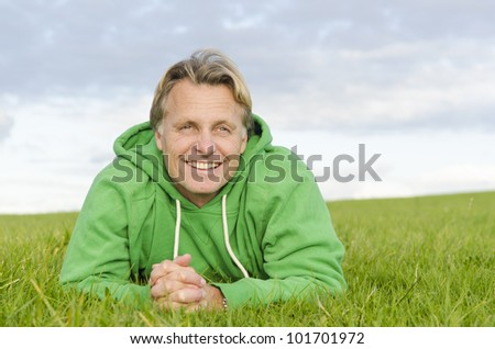 A color portrait photo of a happy smiling blond haired man in his forties laying on the green grass wearing a green colored top. - stock photo