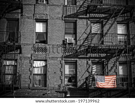 A colored American flag hanging on metal stairs, zigzagging up the side of a brick building. - stock photo
