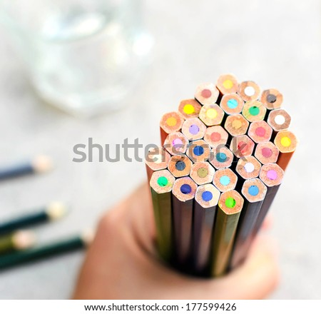 A colored pencil in hand - stock photo