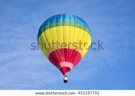 A colorful air balloon is floating in the blue sky. - stock photo
