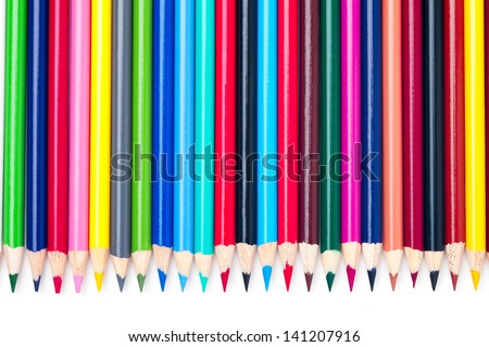A colorful arrangement of pencils crayons on a white background. - stock photo