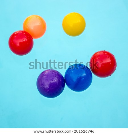 A colorful beach balls floating in a blue swimming pool - stock photo