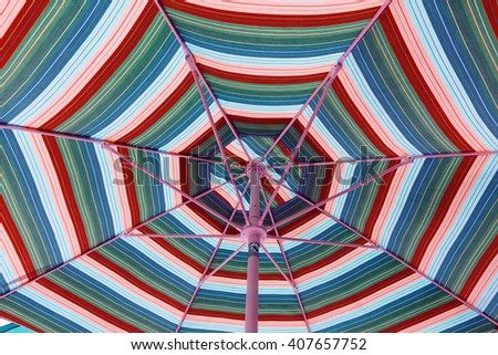A colorful beach umbrella from underneath. - stock photo