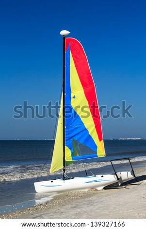 A colorful catamaran on a tropical beach - stock photo