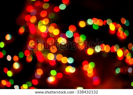 A colorful christmas Light bulb blurred in the dark