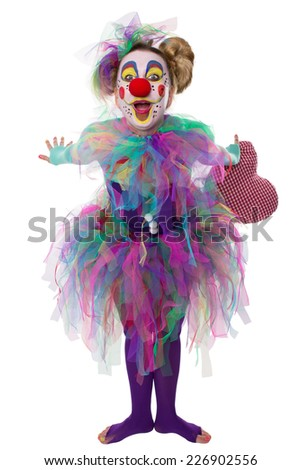 A colorful clown smiling and leaning toward the viewer - stock photo
